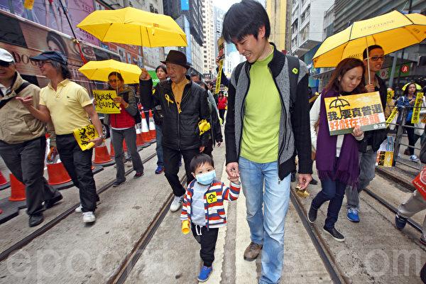 香港民間人權陣線2月1日舉行雨傘運動後首個爭取真普選的大遊行,有一萬三千人參加,有市民帶兒子參加遊行。(潘在殊/大紀元)