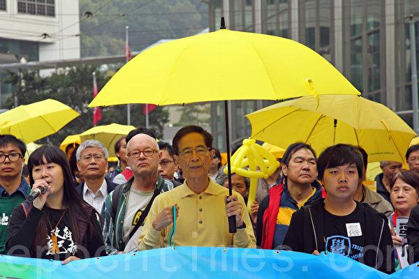 香港民間人權陣線2月1日舉行雨傘運動後首個爭取真普選的大遊行,有一萬三千人參加。民主派元老李柱銘(中)打傘參加遊行。(潘在殊/大紀元)