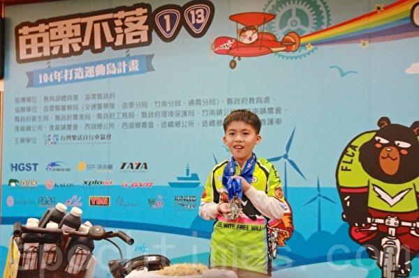 穆宥昇展示之前骑完全程的纪念奖牌。(许享富 /大纪元)