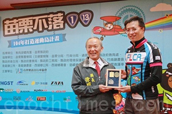 乐活自行车协会理事长戴祖辉赠送历年奖牌给苗栗县长徐耀昌(左1)。(许享富 /大纪元)