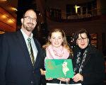 Steve Wharton律师和太太Catherine Wharton带着已跳了六年芭蕾舞的女儿Marie第一次来看神韵。中场休息时﹐Wharton夫妇给女儿买了一本精美的神韵画册。(亦平/大纪元)