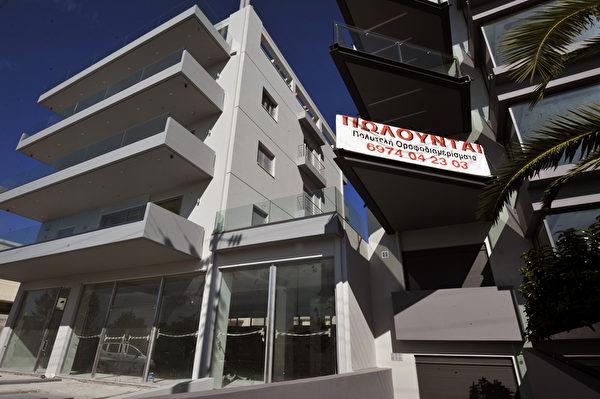 """雅典市中心的新建公寓房打着""""豪华公寓出售""""的广告。据希腊银行透露,无力偿还房贷的希腊人如今越来越多。(LOUISA GOULIAMAKI/AFP/GettyImages)"""