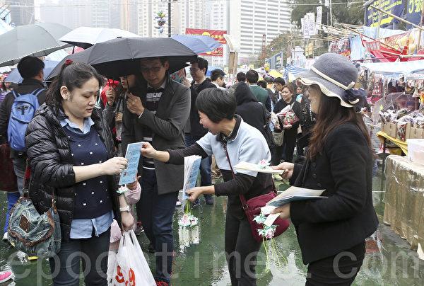 香港维园人头涌涌,有法轮功学员为市民送上小莲花表达新年祝福。(余钢/大纪元)