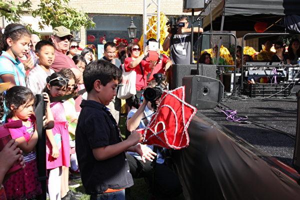 西方观众对中国传统手帕舞非常感兴趣,小男孩现场试转手帕。(徐绣惠/大纪元)