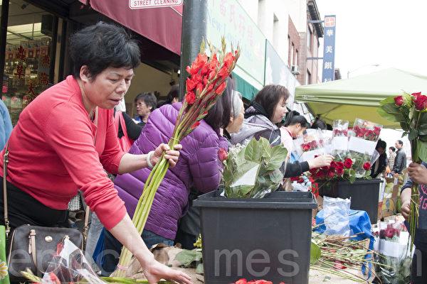 旧金山华埠士德顿街(Stockton Ave.)的中国新年街会,在除夕这天花市火爆,图为华人在选购过年装点之用的鲜花。(周凤临/大纪元)