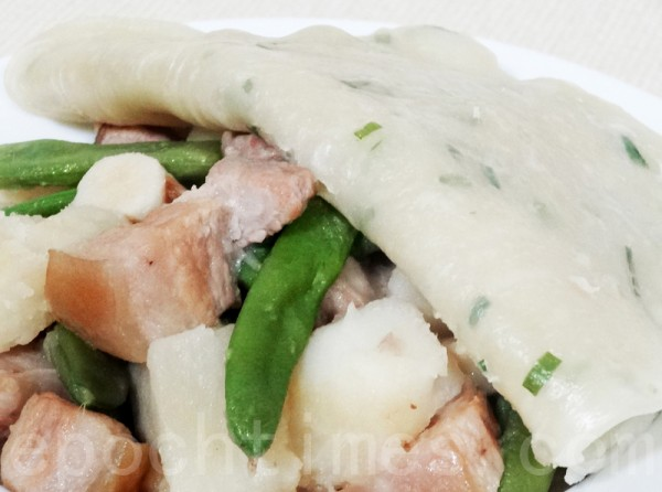 饼皮盖在肉菜上,盖锅焖烧25分钟,使菜炖熟,饼烀好,即可盛盘。(摄影:彩霞/大纪元)