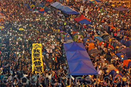 """10月28日傍晚开始,逾万香港人在金钟雨伞广场举行""""雨伞运动满月纪念活动"""",要求真普选,他们撑伞87秒回应警方在9月28日针对市民释放了87个催泪弹。(潘在殊/大纪元)"""