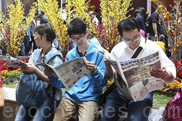 新年期間,大批來港自由行遊客來港購物之餘,亦紛紛爭看大紀元時報。(余鋼/大紀元)