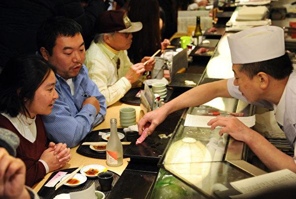 在日本给小费会被视为无礼,甚至是一种羞辱。图为日本民众在餐厅用餐。(YOSHIKAZU TSUNO / AFP)