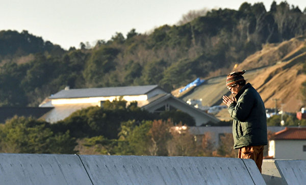 日本11日纪念311东日本大地震4周年,福岛县磐城市1名男子双手合十悼念。(共同社提供)