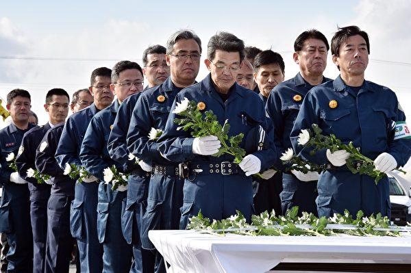 3月11日,警务人员在福岛县东京电力公司福岛第一核电站附近的纪念仪式上,为2011年的地震海啸灾难的受害者献上菊花。(YOSHIKAZU TSUNO/AFP/Getty Images)