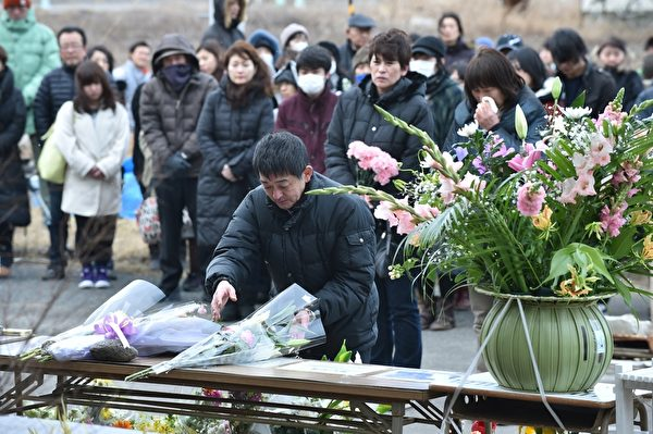 3月11日,宫城县名取市Yuriage初中追悼海啸遇难者的集会上,与会者献上一束鲜花。(KAZUHIRO NOGI/AFP/Getty Images)