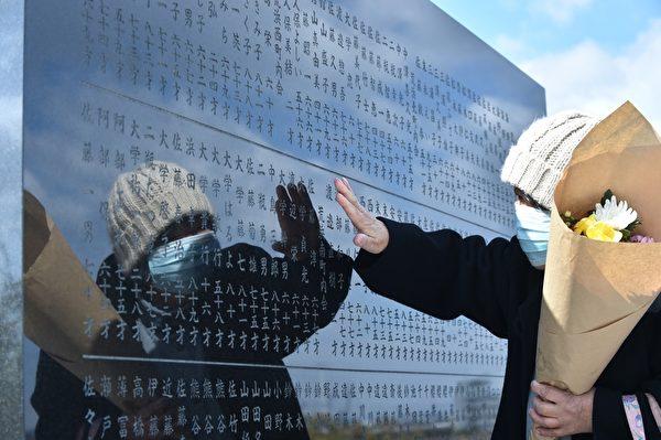3月11日,宫城县仙台市一位女性与为2011年地震海啸灾难的受害者树立的纪念碑。(KAZUHIRO NOGI/AFP/Getty Images)