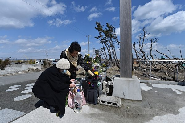 日本大地震4周年,3月11日,人们在宫城县仙台市的沿海地区一个衣冠塚悼念2011年地震海啸灾难的受害者。(Photo credit should read KAZUHIRO NOGI/AFP/Getty Images)