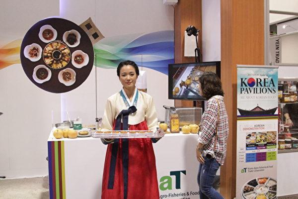 身着传统服装的韩裔女孩在向观众招待现场制作的韩国梨馅饼。(张岳/大纪元)