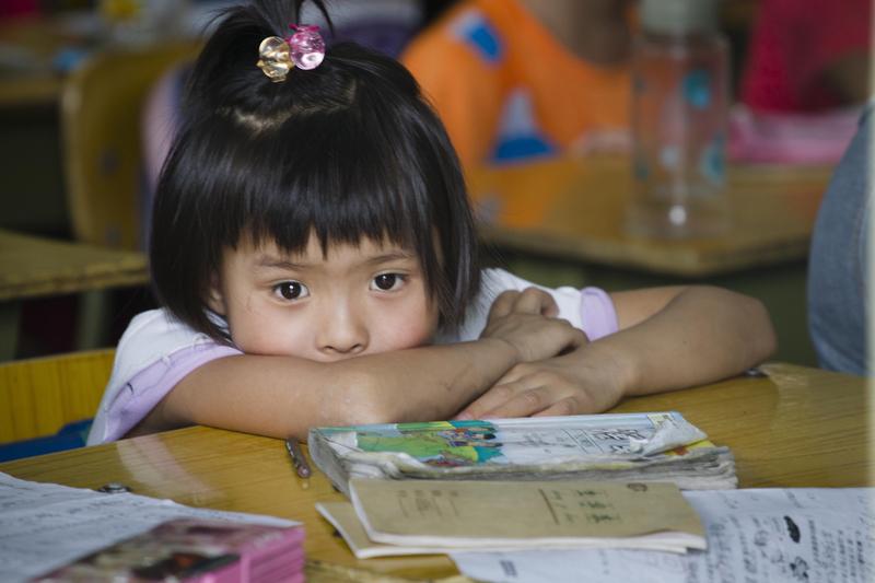 住在北京的一名农民工的孩子,在一间被政府即将强令关闭的农民工子弟小学内。由于没有北京户口,她面临被迫返回家乡才能继续读小学的命运。(STR/AFP/GettyImages)