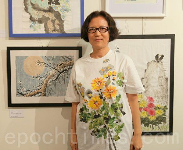 从忧郁变成快乐的女工Vanessa与她的画'月上梅梢'。(摄影:何蔚/大纪元)