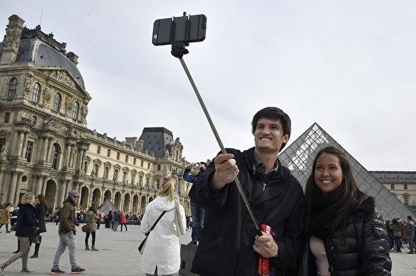 繼美國之後,歐洲多個著名景點亦宣佈禁止遊客使用自拍棒。圖為3月7日,遊客在巴黎盧浮宮前使用自拍棒。(DOMINIQUE FAGET/AFP)