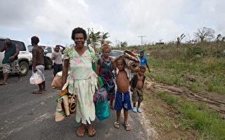 3月16日,瓦努阿图群岛被5级飓风Pam重创两天后,该地区的对外通讯遭切断,几乎无法与外界联络。图为受灾居民沿着马路边行走。(AFP)