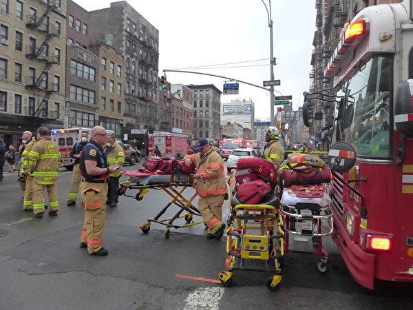 3月26日下午,人口密集的纽约曼哈顿东村(East Village)一建筑物发生爆炸,邻近大楼随后起火,有建筑倒塌。图为安全救护人员带着医药箱、担架等救护设施赶到现场等待救援命令。(蔡溶/大纪元)