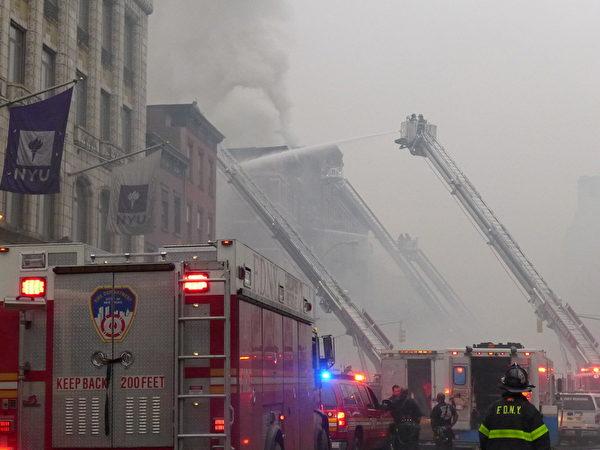 四架消防云梯同时向失火的大楼喷水柱。附近居民说,这些楼宇都有近百年的历史了,事发地点附近是纽约大学(NYU),图中可见NYU的旗子。(蔡溶/大纪元)