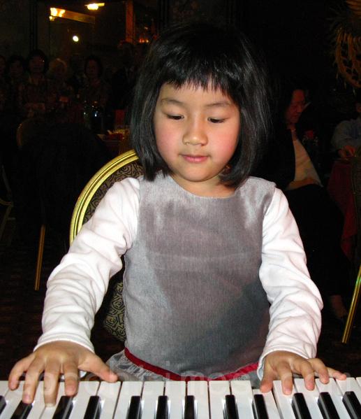 5歲的余靜雯以電子琴演奏助興。(馮文鸞/大紀元)