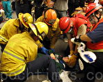 """加州每年举行Shakeout地震演习,图为2010年演习中消防队员在对洛杉矶Providence 高中""""受伤""""学生进行救治。( 摄影:刘菲/ 大纪元)"""