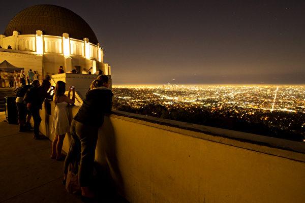 加州洛杉矶,游人从座落于好莱坞山顶的格里菲斯天文台远眺洛城夜景。(JOE KLAMAR/AFP)