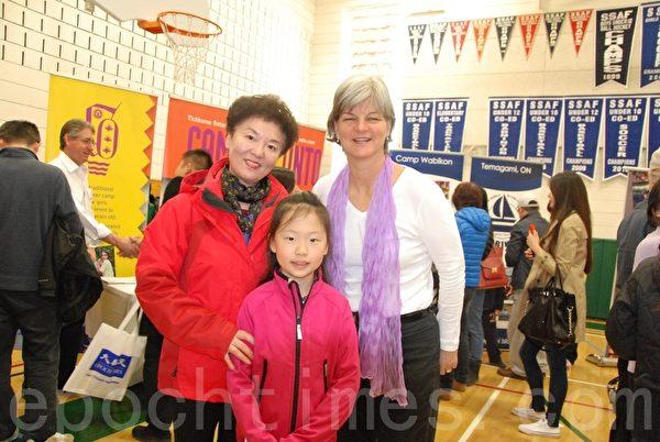 为孙女选择一家女营的刘女士(后左1)现场注册。(伊铃/大纪元)