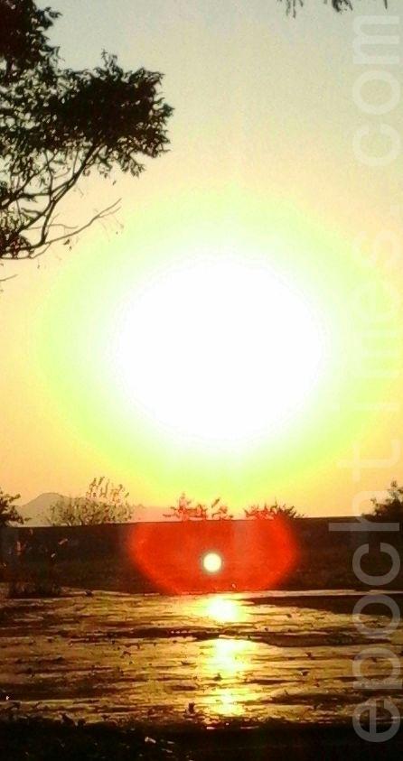 光亮旭日照耀天空,一层层红橘黄绿纯净的光辉围绕太阳,照片中,对映着太阳出现了另一个包着红光晕的光球。(图:大法弟子/大纪元)