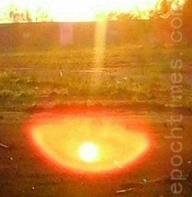 太阳下边出现包着光晕的光球,此时呈现红、橘色晕光。(图:大法弟子/大纪元)