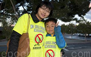 2015年4月7日晚,来参加抗议的谭女士和7岁的儿子Max。(马有志/大纪元)