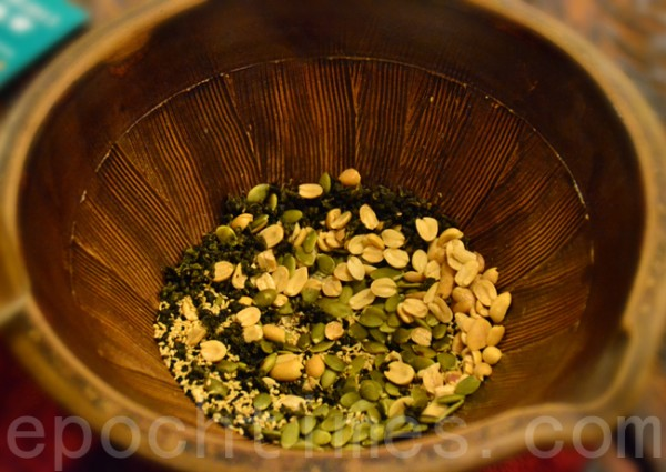 """把茶叶、花生、芝麻…等食材,放进陶土烧成的""""擂钵"""",钵内有沟纹。(彩霞/大纪元)"""