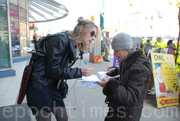 多伦多大学二年级学生Generiere Smith 在义工递过来的征签表上签名。(伊铃/大纪元)
