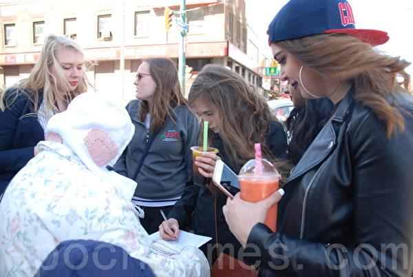"""从美国来加拿大旅游的大学生Rana Rhalil和她的4个同伴听了义工的讲解以后欣然在征签表上签名,并说:""""我们支持正义,反对邪恶。""""(伊铃/大纪元)"""