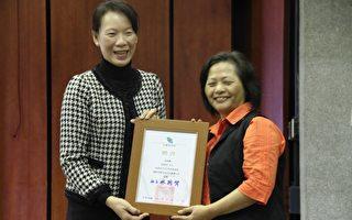 林素云夫人(左)颁发证书给何明雪女士(右)。(谢月琴/大纪元)