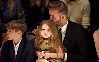 贝克汉抱着女儿看秀,还不时闻头发、亲亲,展现满满的父爱。(Jeff Vespa/Getty Images for Burberry)