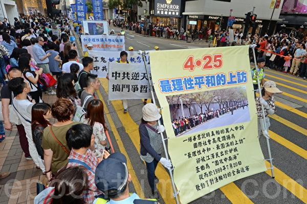 香港法輪功學員25日在長沙灣發起「四二五」16周年反迫害集會遊行,浩蕩的遊行隊伍經過鬧區,吸引許多民眾和大陸遊客觀看。(宋祥龍/大紀元)