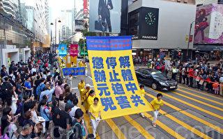 """香港法轮功学员4月25日举行纪念""""四.二五""""和平上访16周年及声援二亿人退出中共组织集会游行。八百人组成的游行队伍场面浩大,震撼了许多大陆游客,他们纷纷拿起相机拍照。(潘在殊/大纪元)"""