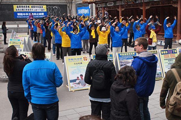 2015年4月25日,蒙特利爾法輪功學員在唐人街中山公園舉行煉功講真相活動,紀念「4·25」法輪功和平上訪16週年,法輪功學員祥和的煉功動作吸引眾多路人駐足觀看並了解真相。(Nathalie Dieul/大紀元)
