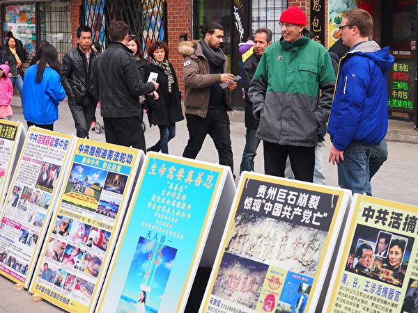2015年4月25日,蒙特利爾法輪功學員在唐人街中山公園紀念「4·25」法輪功和平上訪16週年,路人駐足了解真相。(Nathalie Dieul/大紀元)