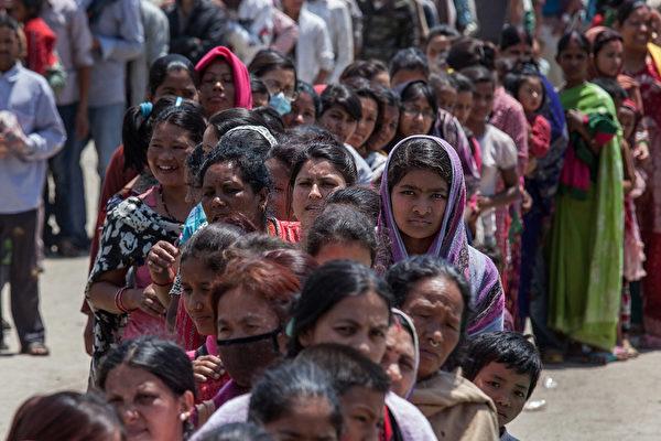 4月27日,一场7.8级地震后,尼泊尔首都加德满都的民众排队领取食物。(Omar Havana/Getty Images)