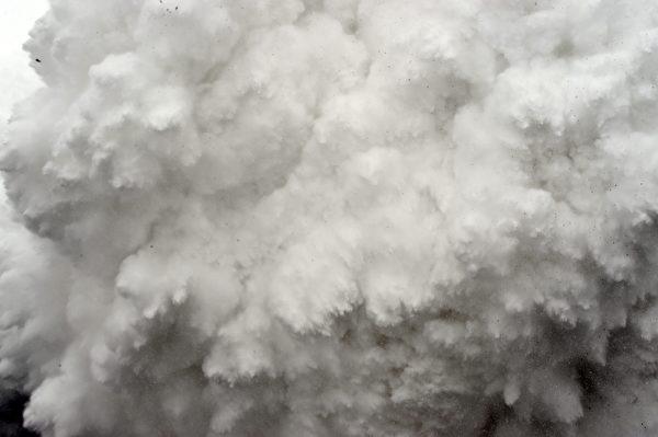 图为2015年4月25日,尼泊尔发生7.8级地震引发珠穆朗玛峰雪崩,巨大的雪团尘尘滚滚上天空数百英尺高,许多人被飞奔而来的雪、岩石和瓦砾击中,帐棚也飞起来。所有的人都被雪覆盖住。ROBERTO SCHMIDT/AFP/Getty Images)
