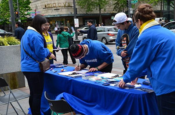 西雅圖民眾在反迫害簽名表上簽名。(舜華/大紀元)