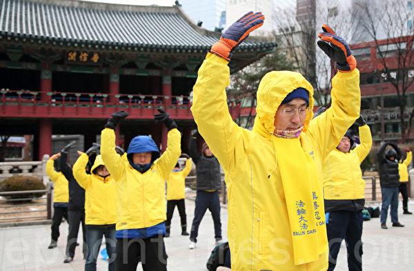 2014年12月7日,韩国法轮功学员在严寒中集体炼功。(大纪元)