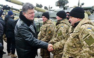 乌克兰总统波罗申科2014年12月6日宣布,根据初步达成的协议,谈判各方将于9日于白俄罗斯首都明斯克再进行和谈。图为他在乌克兰东北部的城市检阅军队的军事装备时,与军人握手。(SERGEY BOBOK/AFP/Getty Images)