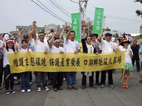 民眾手持抗議布條遊行。(廖素貞/大紀元)