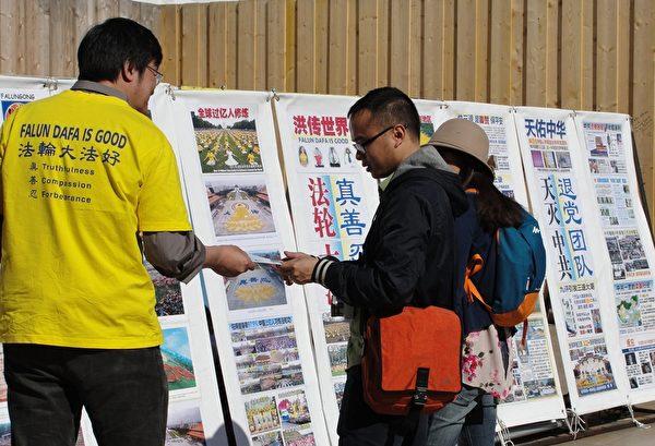 两位中国游客在了解真相。(李婉清/大纪元)