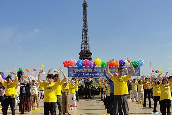 法国法轮功学员在铁塔下展示功法。(李婉清/大纪元)