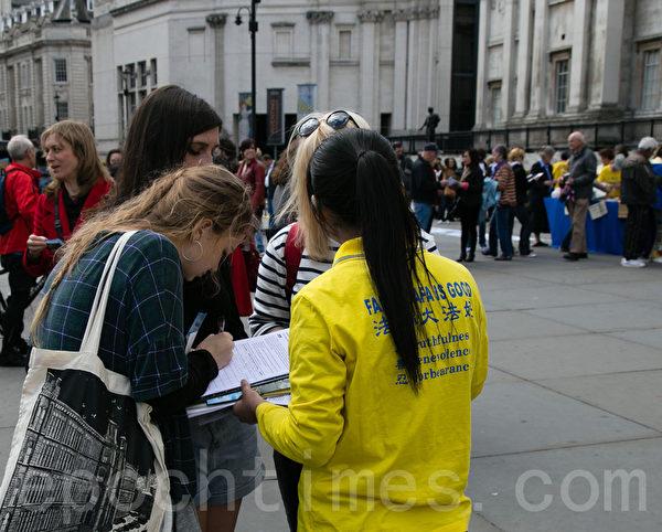 行人听闻法轮功在大陆受迫害的真相,在征签表上签名。(罗元/大纪元)